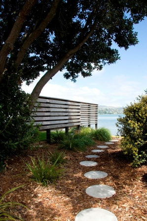 "Rough sawn uneven width macrocarpa slats provides a visual buffer while allowing the planting to ""pass underneath""."