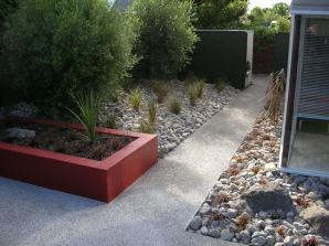 "Simple, strong, low maintenance design solution. Canterbury themed, exposed aggregate greywacke concrete paving, concrete masonry block planter, loose boulder aggregate ""mulch"". Local native plants."